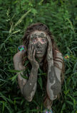 Muddy Amazon-Mädchen, das sich im Wald hinter einem Busch, während Seifenblasen fliegen um sie versteckt Lizenzfreies Stockbild