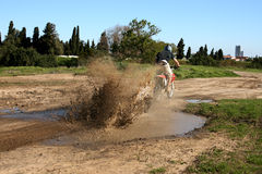 Muddy Biker. Young biker riding through a muddy puddle creating a splash Stock Photo