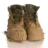 Muddy boots. Muddy work boots isolated on a white background stock photo