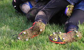 Muddy boots. Close up view of of muddy rugby boots showing studs, soil and grass on an obviously muddy game royalty free stock photography