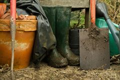 Muddy boots and spade. Wellington boots, waterproof and spade drying out in the greenhouse after a wet day in the garden royalty free stock image