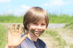 Muddy boy. Smiling boy with mud on his face and hand Stock Photography