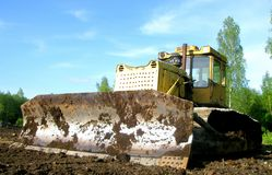 Muddy Bulldozer Blade. Small earth mover or bulldozer covered in dirt and mud royalty free stock photo