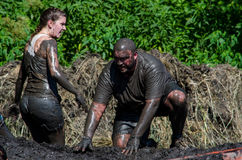 Muddy couple. A muddy couple struggle over a muddy hill top, as they participates in the 2013 marathon called a Mudathlon, in northwest Indiana Royalty Free Stock Image