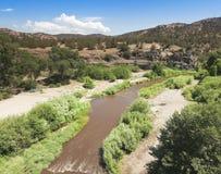 A Muddy Creek Runs Through a Canyon Royalty Free Stock Photos