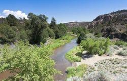 A Muddy Creek Runs Through a Canyon Stock Images