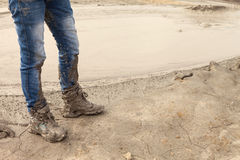 Muddy and dirty Hiking Boots and blue jeans Royalty Free Stock Photography