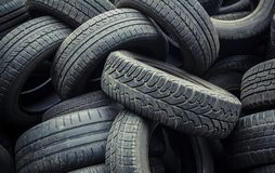 Muddy, dirty, worn car tires pile. Used car tires pile in the tire repair shop yard royalty free stock photography