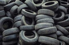 Muddy, dirty, worn car tires pile. Used car tires pile in the tire repair shop yard Stock Image