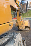Muddy excavator shovel with rear-view mirror at construction are Royalty Free Stock Photo