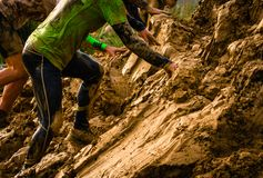 Muddy obstacle race runner in action. Mud run royalty free stock photos