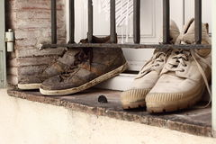Muddy fashion trainers drying on a window sill. Vintage retro look. Stock Photos