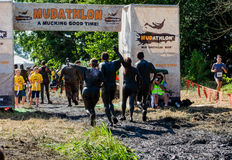 Muddy finish. A group of dirty people are muddy but victorious as they cross the fiunish line in the 2013 marathon called a Mudathlon, in northwest Indiana Stock Photo
