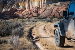 Muddy four-wheel drive vehicle on curving dirt road driving towards colorful cliffs in a high desert landscape stock image