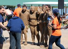Muddy Group of People Poses for Picture after completing a Mud Run. Heavily Mudded Group of people pose for picture after completing an obstacle course after Stock Photo