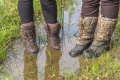 Muddy Hiking Boots em uma poça da água Foto de Stock Royalty Free