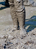 Muddy legs. An athlete stands, dripping and muddy, at  the  July 2014 mudathlon, in northwest Indiana Stock Photos
