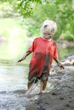 Muddy Little Boy Playing Outside in de Rivier stock afbeeldingen