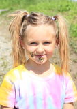 Muddy little girl. Portrait of a smiling little girl with ponytails in colorful t-shirt with mud on her face royalty free stock photography