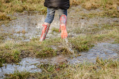 In muddy meadow in rubber boots Royalty Free Stock Photography