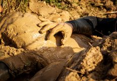 Muddy obstacle race runner in action. Mud run. Details of the hands stock image