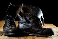 Muddy old military boots. Black color, dirty soles. Wooden table Stock Images