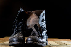 Muddy old military boots. Black color, dirty soles. Wooden table Royalty Free Stock Photography