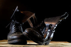 Muddy old military boots. Black color, dirty soles. Wooden table Stock Photography