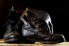 Muddy old military boots. Black color, dirty soles. Wooden table Stock Image
