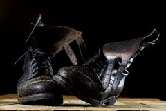 Muddy old military boots. Black color, dirty soles. Wooden table Stock Photos