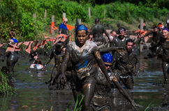 Muddy racers in a competition. Racers  wade through a muddy river in the 2013 marathon called a Mudathlon, in north west Indiana Royalty Free Stock Image
