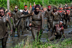 Muddy racers. Mud covered people race in a 2013 marathon called a Mudathlon Stock Photography