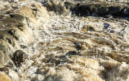 Muddy rapid flowing over rocks Royalty Free Stock Image