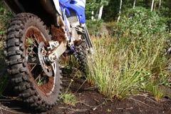 Muddy rear wheel of dirt bike Stock Photos