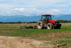 Muddy red tractor with its plow on trailer in a just plowed agricultural field. Faraway mountains on background.  Stock Photography
