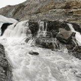 Muddy river with waterfall flowing from below the glacier stock photography
