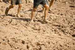 Muddy Runners. Group of runners on a muddy trail. The image orientation is vertical and there is copy space Stock Image