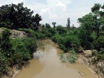 Muddy Rural River Monzón-crecido en la ciudad antigua Bhaktapur Imágenes de archivo libres de regalías