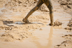 Muddy Splash. Mud covered shoes and legs on a muddy trail. The image orientation is horizontal and there is copy space Royalty Free Stock Images