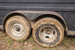Muddy tires of a cattle or horse trailer sitting on grass with mud splattered up side stock photography