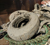 Muddy Tires in a Dumpster Collected After A Cleanup Event. Muddy trash - including tires, rope, wood, and metal - collected by volunteers during a river cleanup stock images