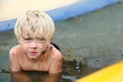 Muddy Toddler Boy Outside in Baby Swimming Pool. A muddy little 3 year old toddler boy is looking serious as he washes off the dirt outside in a baby swimming Royalty Free Stock Photography