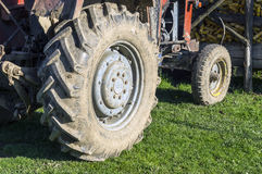 The muddy tractor wheel after working in the field Stock Photo