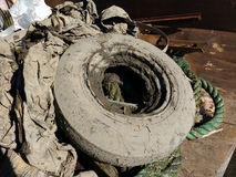 Muddy Trash in a Dumpster Collected After A Cleanup Event, Tire Covered in Mud Stock Photos