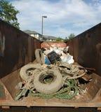 Muddy Trash i en avfallscontainer som samlas under en rengöringshändelse, gummihjul som täckas i gyttja Royaltyfri Bild