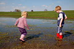 Muddy. Two kids walking trough a muddy puddle Royalty Free Stock Images