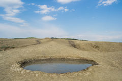 Muddy volcano crater. Muddy volcano round crater filled with mud and beautiful blue sky in the background royalty free stock photo