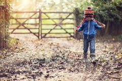 Muddy walk. Boy walking on muddy footpath in autumn at sunset royalty free stock photos