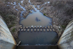 Muddy water outlet and damn Stock Image