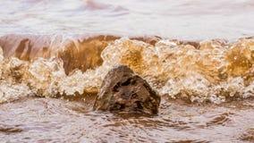 Muddy Water Waves Hitting ein Felsen, Panshet stockbilder